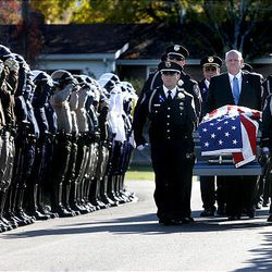 The funeral procession for North Salt Lake Police Officer Charlie Skinner enters Bountiful City Cemetery past an officers' honor guard.