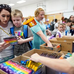 Stephanie Walker and her son, Xander, 5, pick out free school supplies as Liz Magalong, a military spouse and a leader in Cub Scout Pack 55, organizes boxes during Operation Homefront's annual Back-to-School Brigade event at Hill Field Elementary in Clearfield on Tuesday, Aug. 13, 2019.