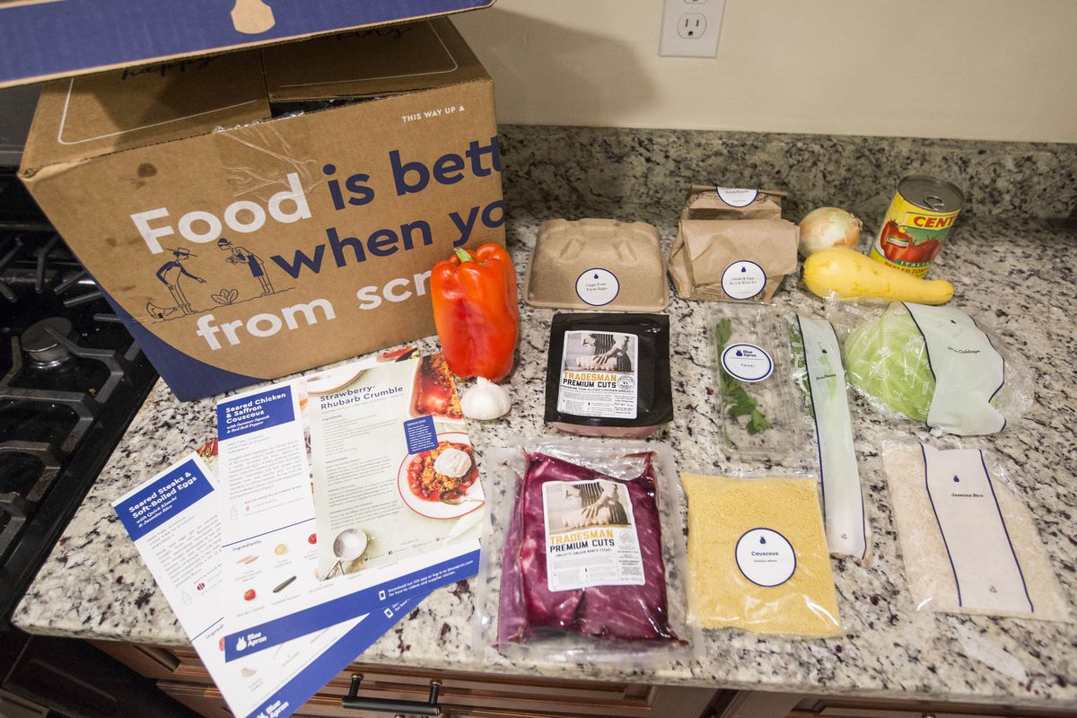 Food from meal delivery kit company Blue Apron is spread out over a counter top in a kitchen with the shipping box in the background.