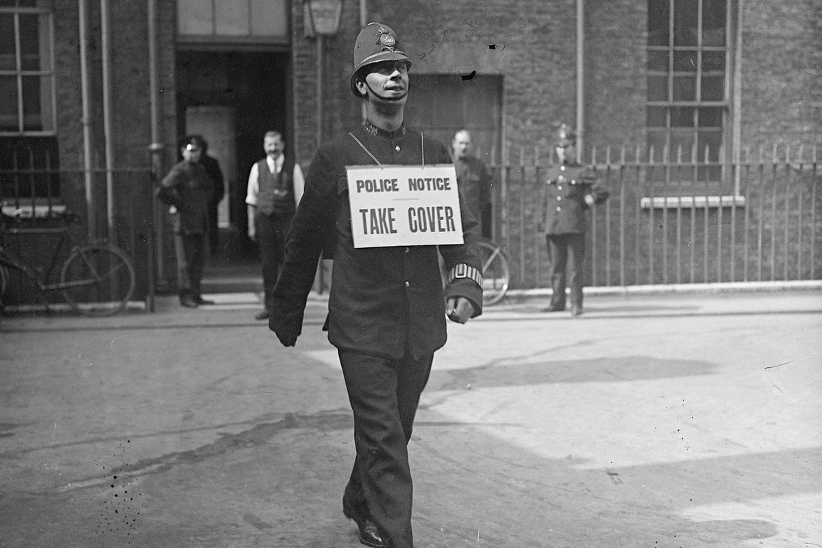 """A police officer wearing a """"take cover"""" sign."""