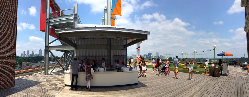 A rooftop boardwalk with games and people drinking.