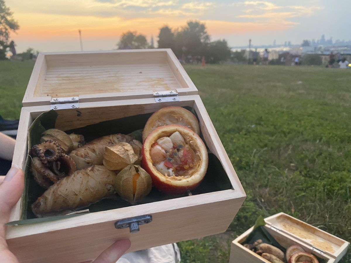 A wooden box of food held up to the camera with a second box of food in the background