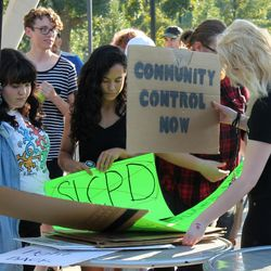 Protestors pick out signs during a rally in Salt Lake City on Saturday, Sept. 2, 2017. Nearly 100 people gathered to protest police conduct against a University Hospital nurse who refused to allow a blood draw from an unconscious patient.