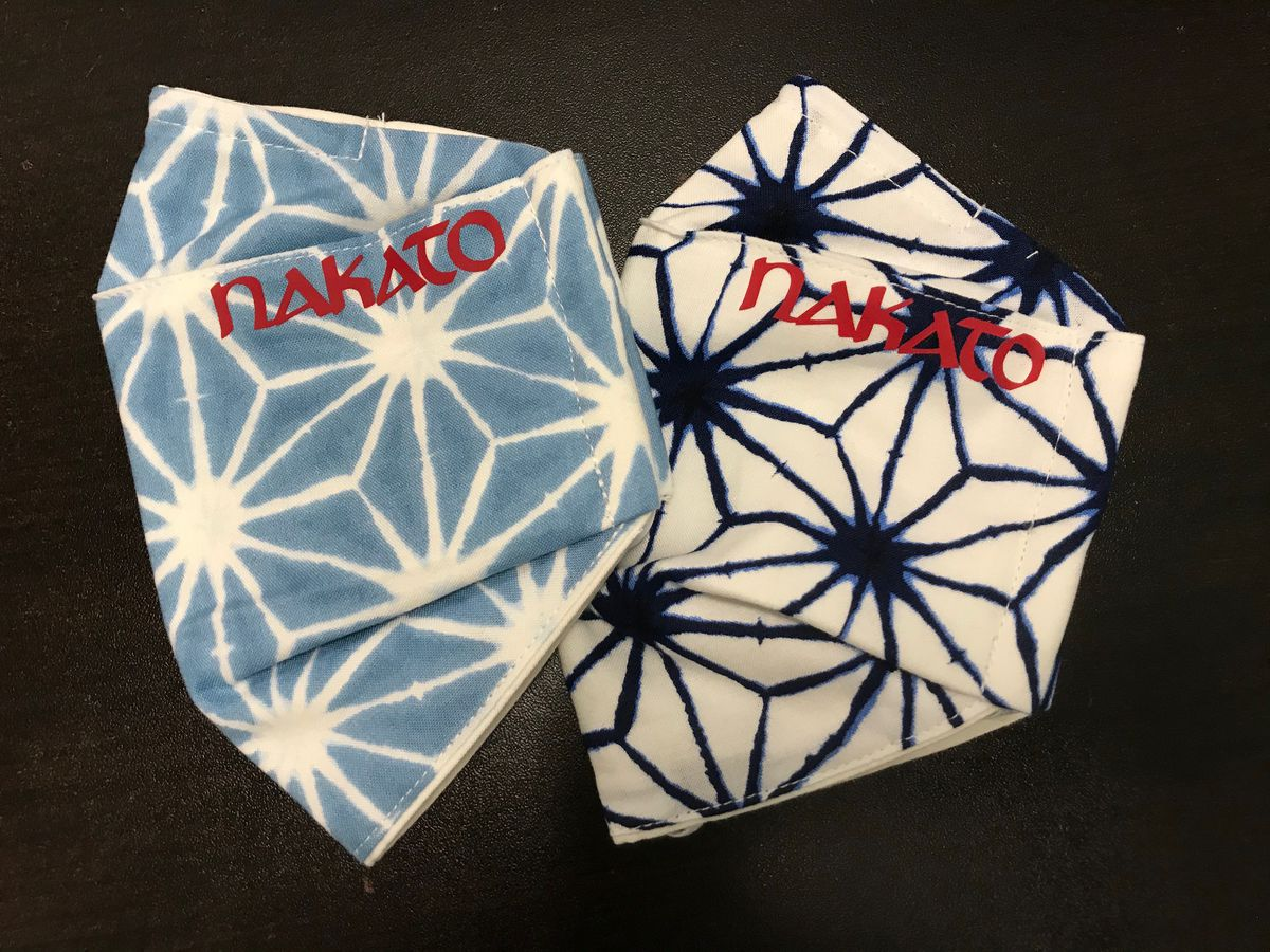 Two Japanese-inspired patterned masks in shades of blue with the Nakato restaurant logo in Atlanta