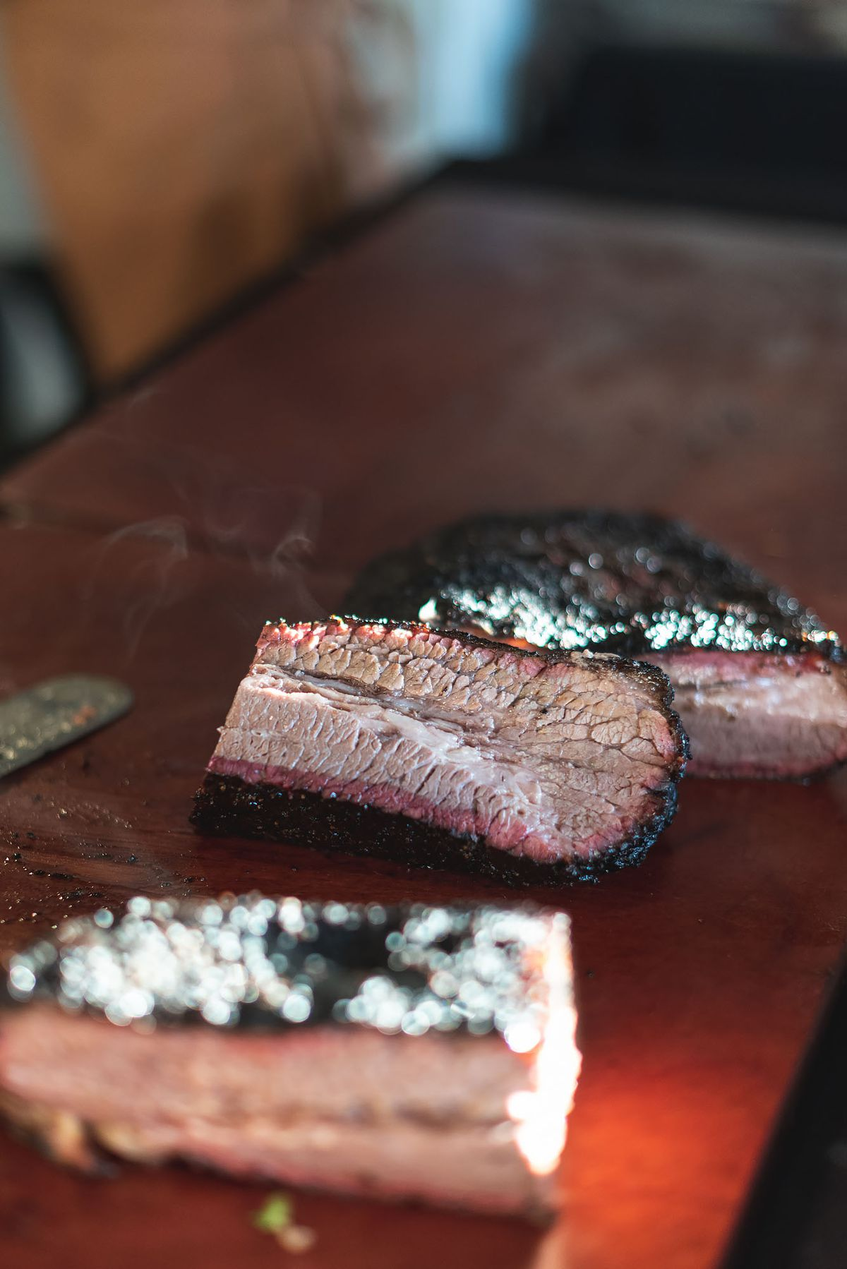 A slice of beef brisket smokes after just being cut.