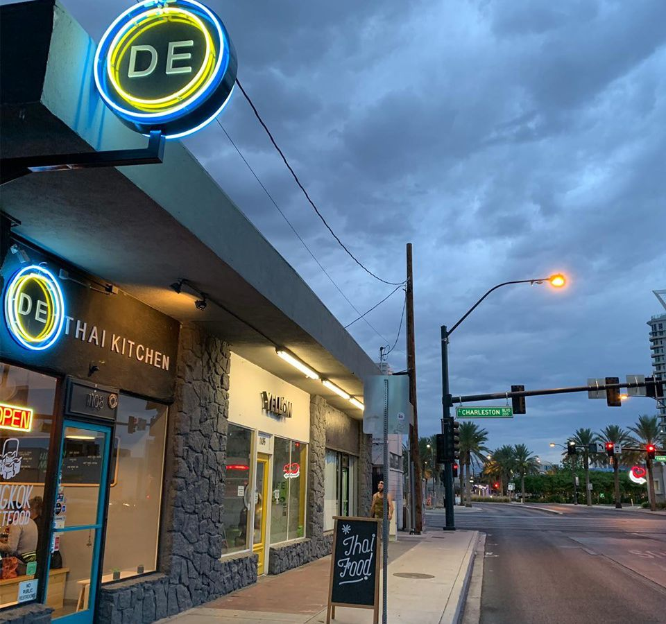 Restaurant exterior showing a neon sign that says D E, a cloudy sky at dusk and a city sidewalk