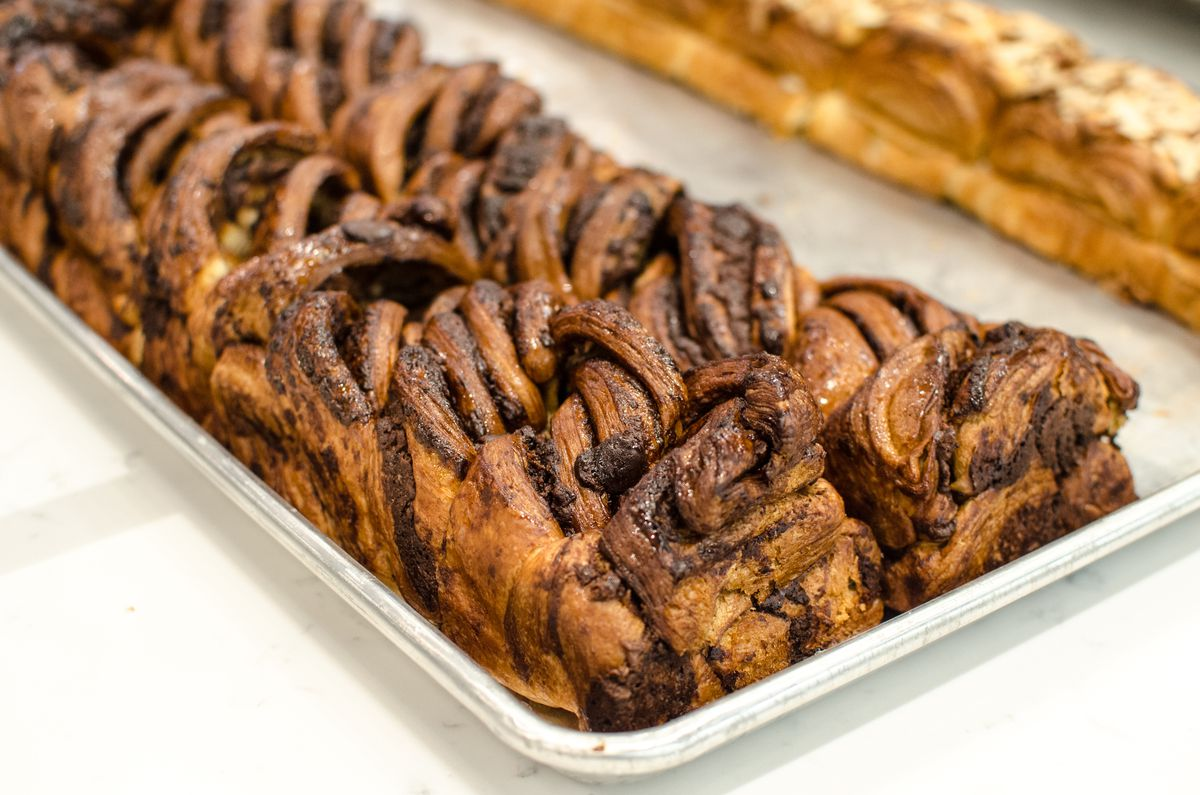 Two long, narrow loaves of chocolate babka sit side by side on a silver tray, cutting diagonally across the front of the photo. In the background, almond babka is a bit visible.