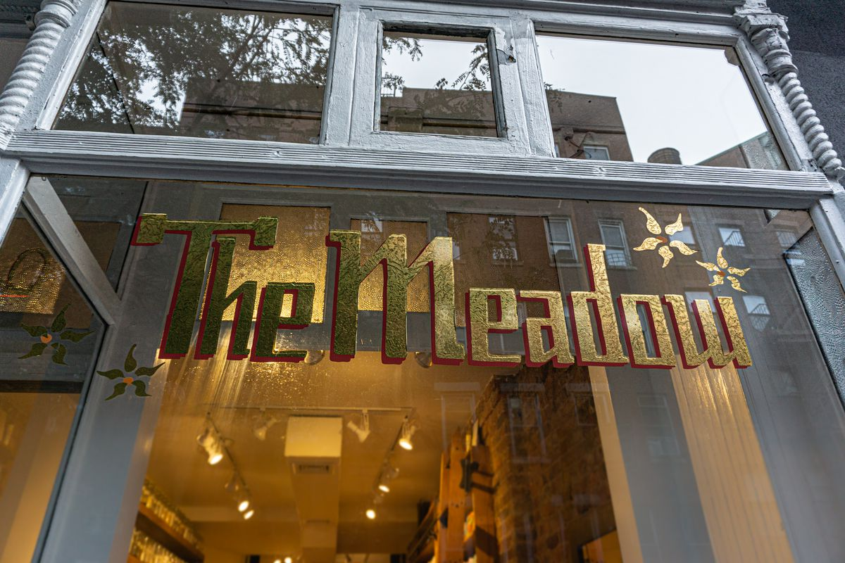 """A window storefront with gold lettering on the glass that reads """"The Meadow"""""""