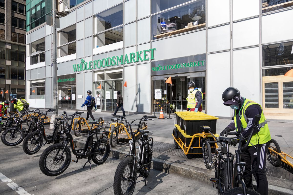 Several bicycles are parked alongside the sidewalk in front of a Whole Foods store. One delivery can be seen filling things into a bicycle carry bag