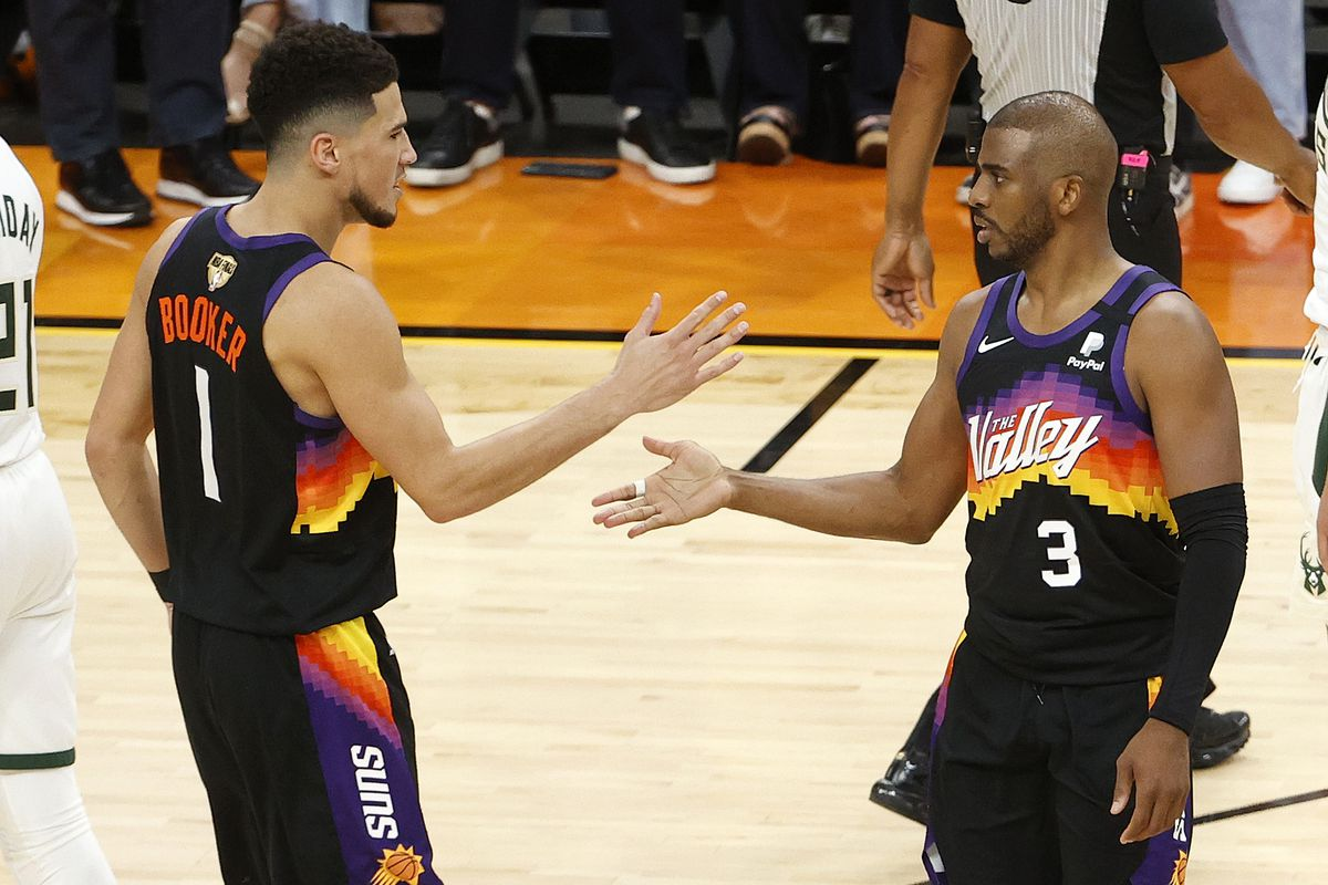 Devin Booker #1 and Chris Paul #3 of the Phoenix Suns celebrate during the second half in Game One of the NBA Finals against the Milwaukee Bucks at Phoenix Suns Arena on July 06, 2021 in Phoenix, Arizona.