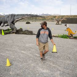 """Drew Latham sets a cone line before the opening of """"Jurassic Quest Drive Thru"""" at the USANA Amphitheatre in West Valley City on Friday, April 23, 2021."""