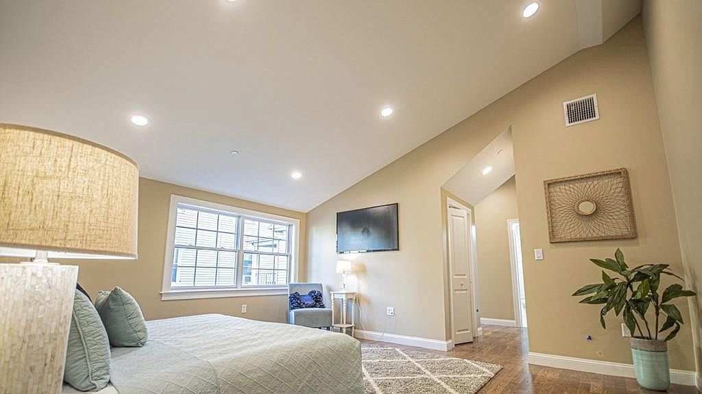 A large bedroom with a bed and lots of lighting.