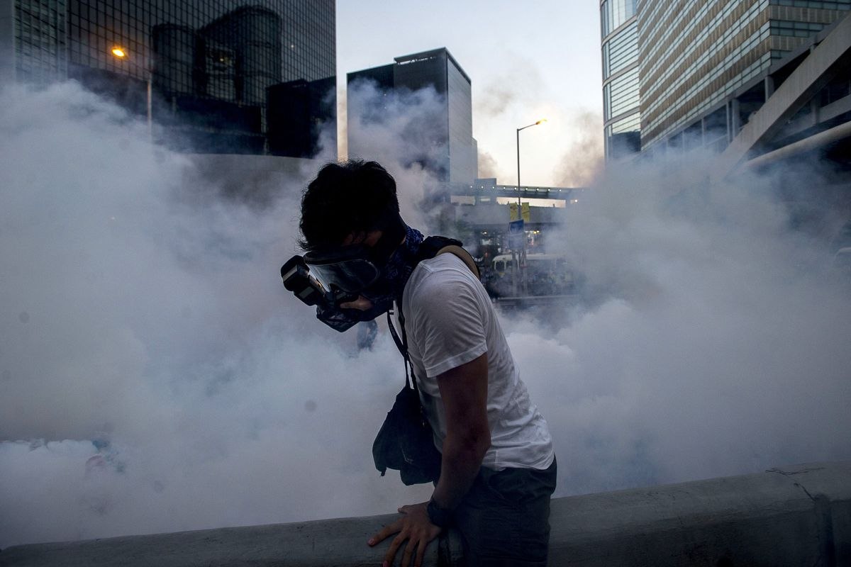 A photographer tries to work amid tear gas in Hong Kong