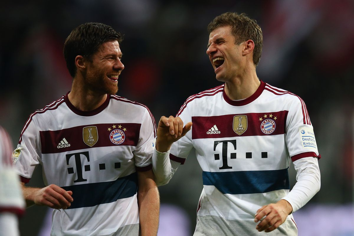 Thomas Müller and Xabi Alonso share a laugh at Manchester United's expense.