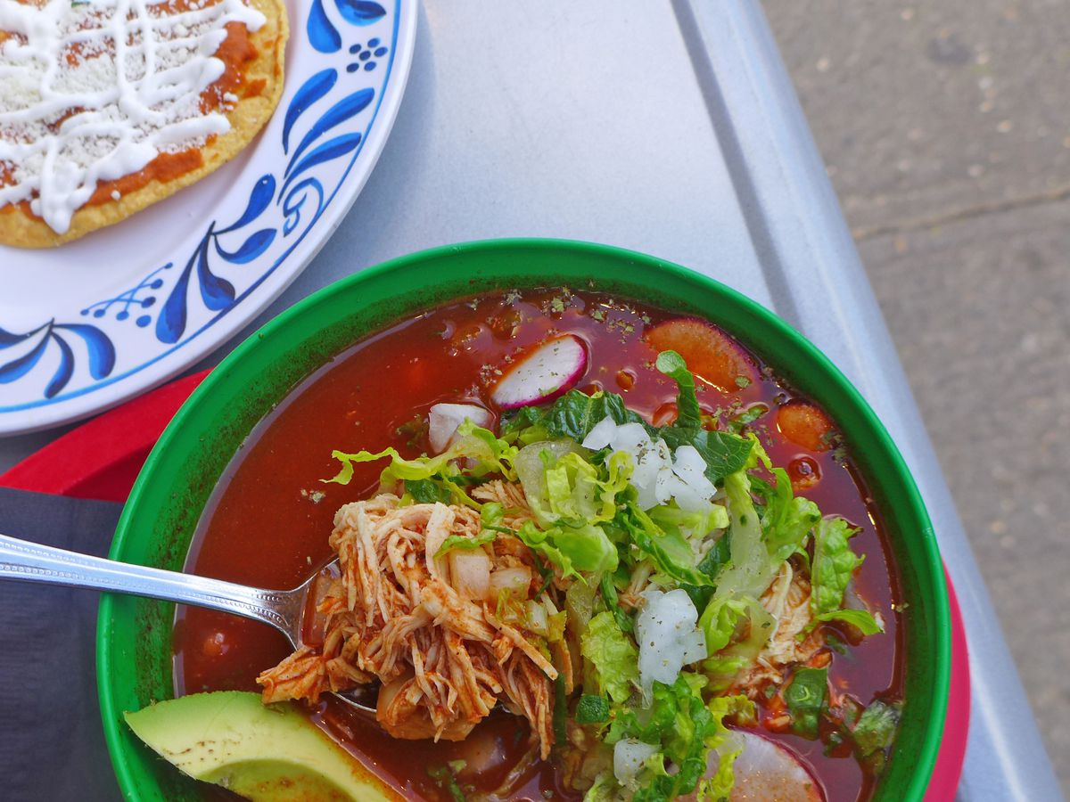 A bowl of bright red soup with shredded chicken being lifted out and a green avocado wedge visible.