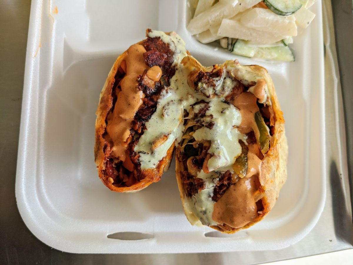 A heavily-sauced seafood burrito sits inside of a takeout container.