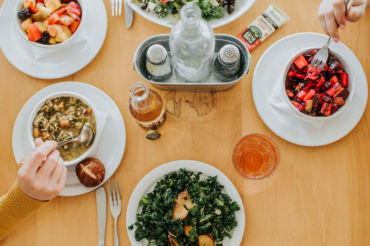 A bowl of soup, two bowls of fruit, a beer, a glass of wine, and a kale salad on the table