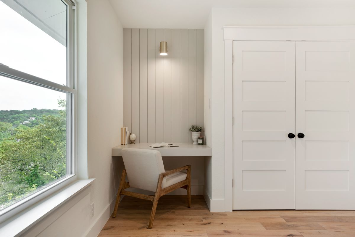 A small built-in desk backed my shiplap is next to a closet in the corner of a secondary bedroom. A brass light is mounted from the wall overhead.