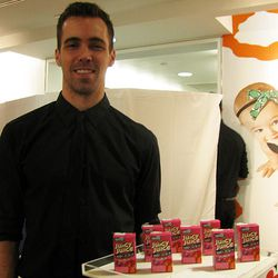 Here is a waiter carrying a tray full of juice boxes.