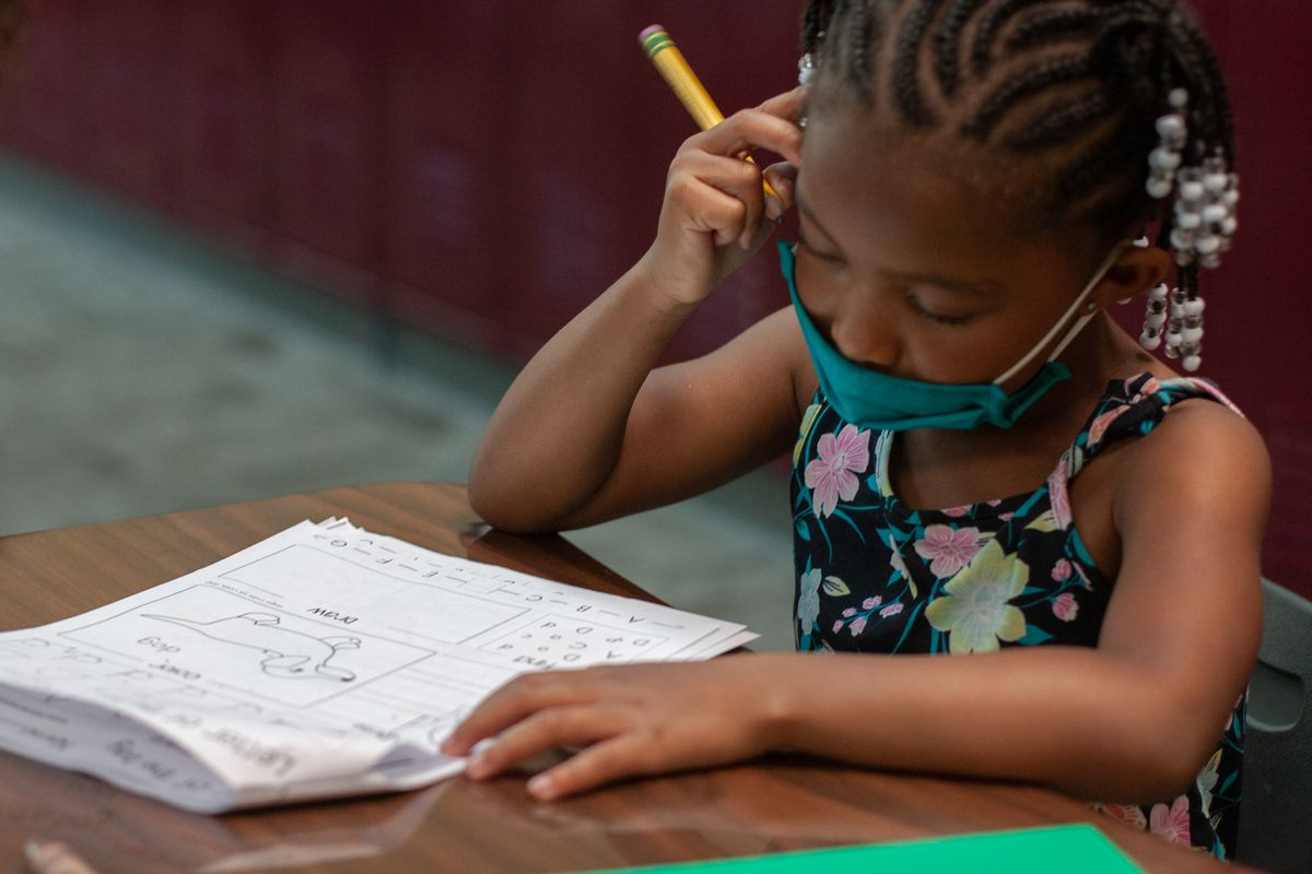 A kindergarten student starts a worksheet about words that begin with the letter D at Kindergarten Kickstart, a summer program at Tindley Genesis Academy in Indianapolis. The program is meant to provide a jump start for students to help them transition to their first school year.