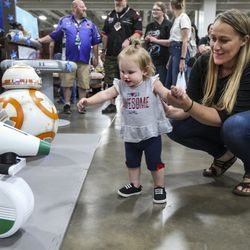 Tayla Trudo, 1, checks out a pair of fully functioning RC droids with the help of her mom Michelle Trudo during the first day of FanX at the Salt Palace Convention Center in Salt Lake City on Thursday, Sept. 5, 2019.