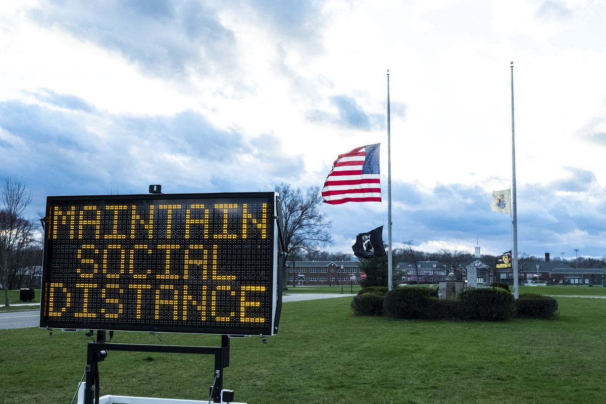 "The American flag flies at half-mast in New Jersey, behind a sign that reads, ""Maintain social distance."""