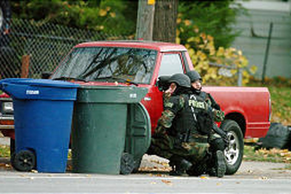 SWAT team members take cover behind a truck outside the house where suspect was thought to be hiding.