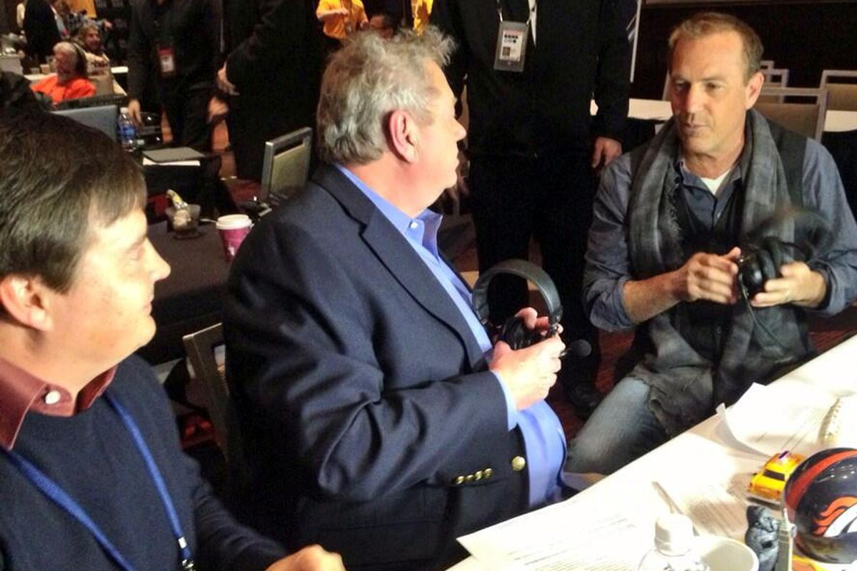 The Denver Post's Troy Renck, left, and Woody Paige speak with Kevin Costner during Super Bowl media week in New York.
