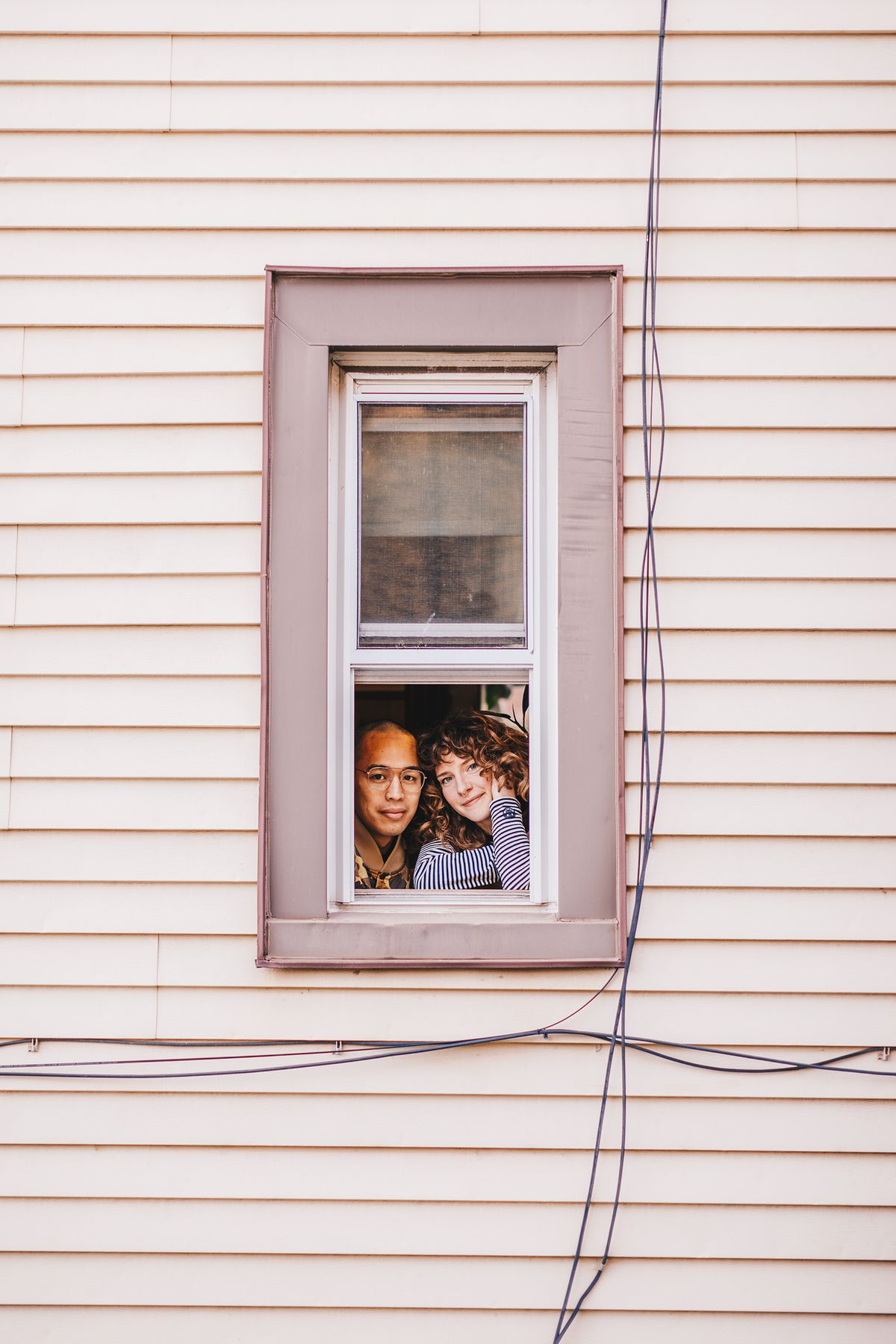 David Yanong Beltran and Diana Bowden peer out their window in Logan Square.