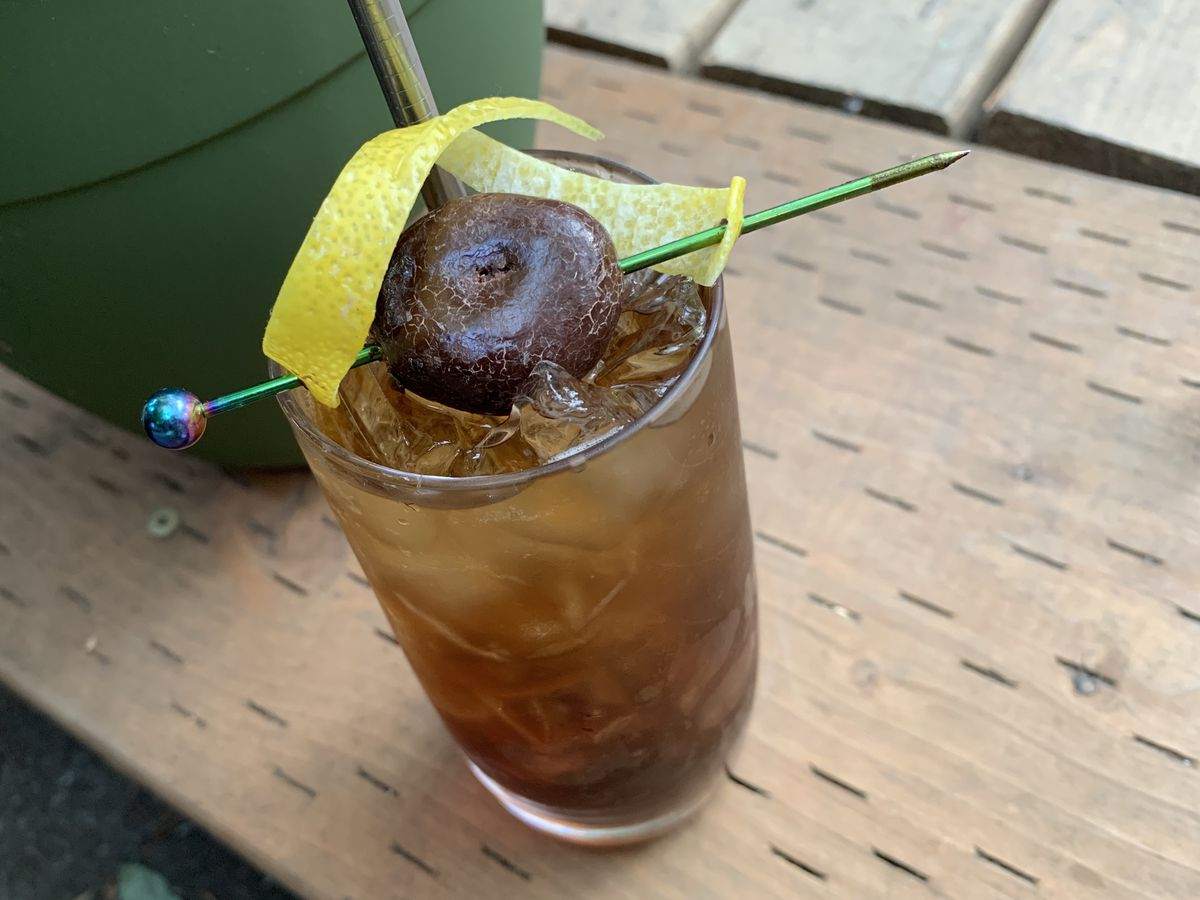 A Collins glass is shot from top-down, with a large, chocolate covered cherry skewered across the top of the glass with a long pin, and topped with a lemon peel. The drink itself is a dark brown sparkling drink.