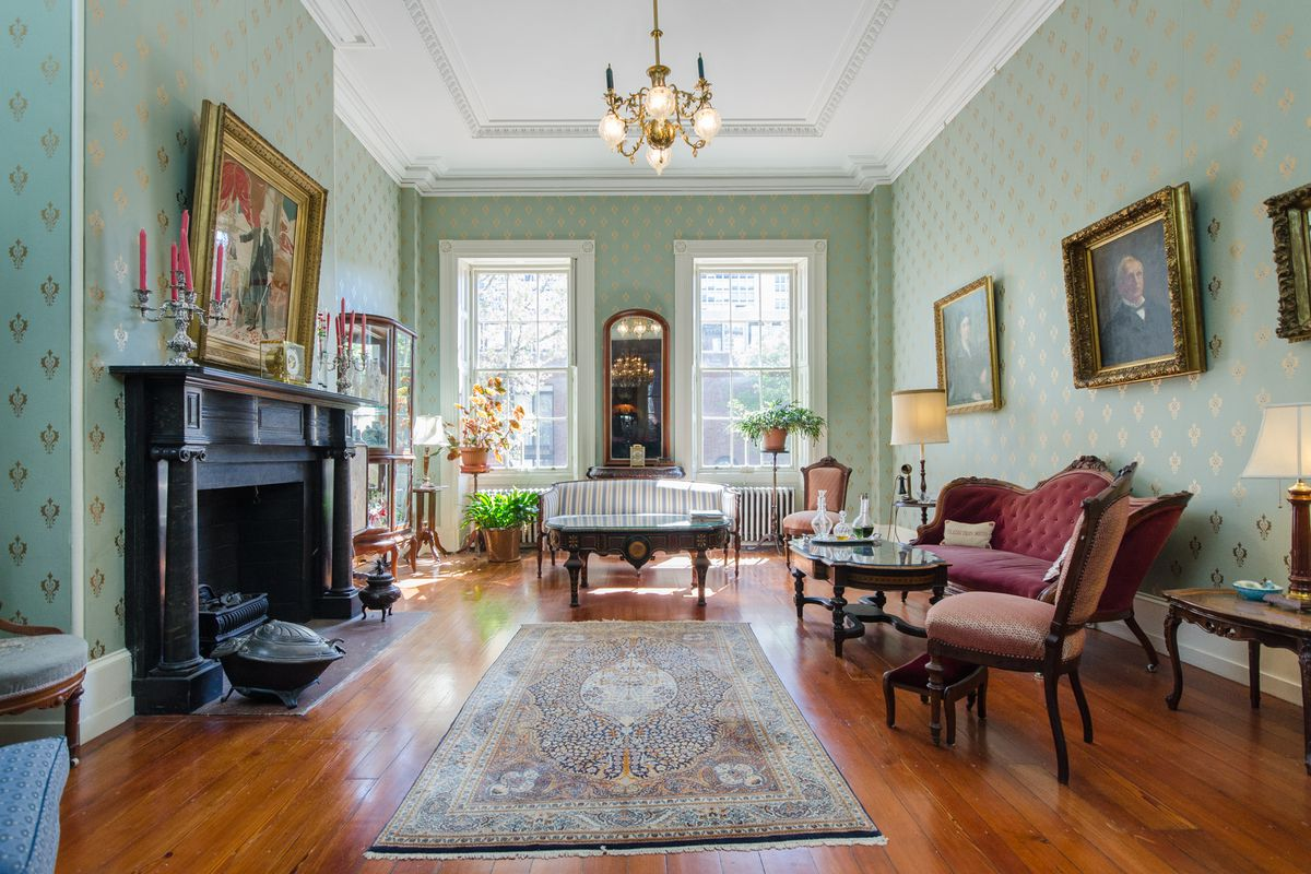 A living room in the John Penn mansion with a chandelier, hardwood floors, and portraits on the walls.