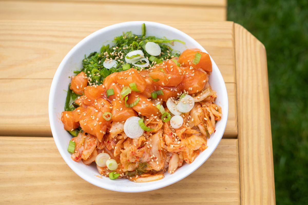 A white bowl full of diced salmon, kimchi, and green onions