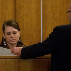 Martin Bond's ex-wife Rachel Bingham reviews a piece of evidence handed to her by prosecutor Tim Taylor while testifying on the first day of Bond's trial in 4th District Court in American Fork Wednesday, Jan. 16, 2013. Bond is accused of killing former BYU professor Kay Mortensen in November 2009.