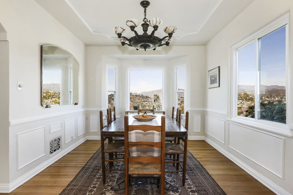 A dining room with a dining table. Big windows and a mirror make it seem like the views are nearly panoramic.