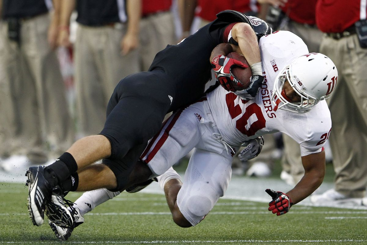 Sep 8, 2012; Foxborough, MA, USA; Indiana Hoosiers running back D'Angelo Roberts (right) is tackled by Massachusetts Minutemen defensive back Joe Colton (left) during the second half at Gillette Stadium.  Mandatory Credit: Mark L. Baer-US PRESSWIRE