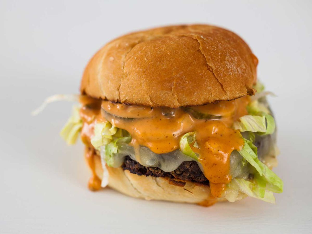 A veggie burger with heaps of lettuce oozing out melted cheese on a blank, bright background
