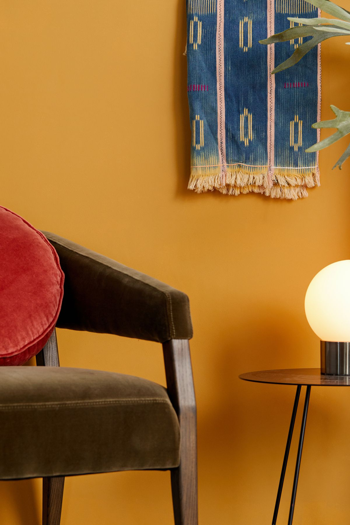 Chair and lamp in front of yellow wall