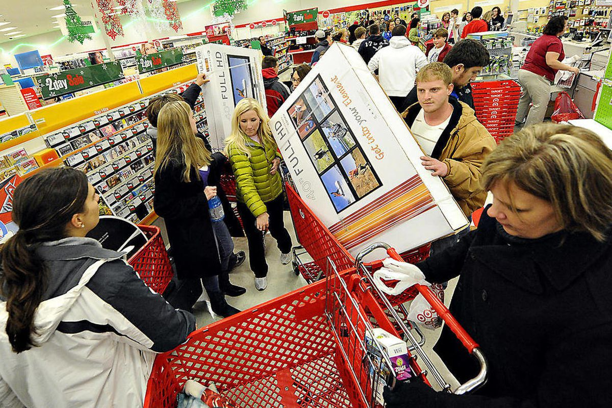 FILE - In this Nov. 25, 2011 file photo, shoppers scramble for door buster deals at Target, in Bowling Green, Ky. Americans increased their spending more slowly in March 2012, suggesting some could be worried about the economy. The Commerce Department sai