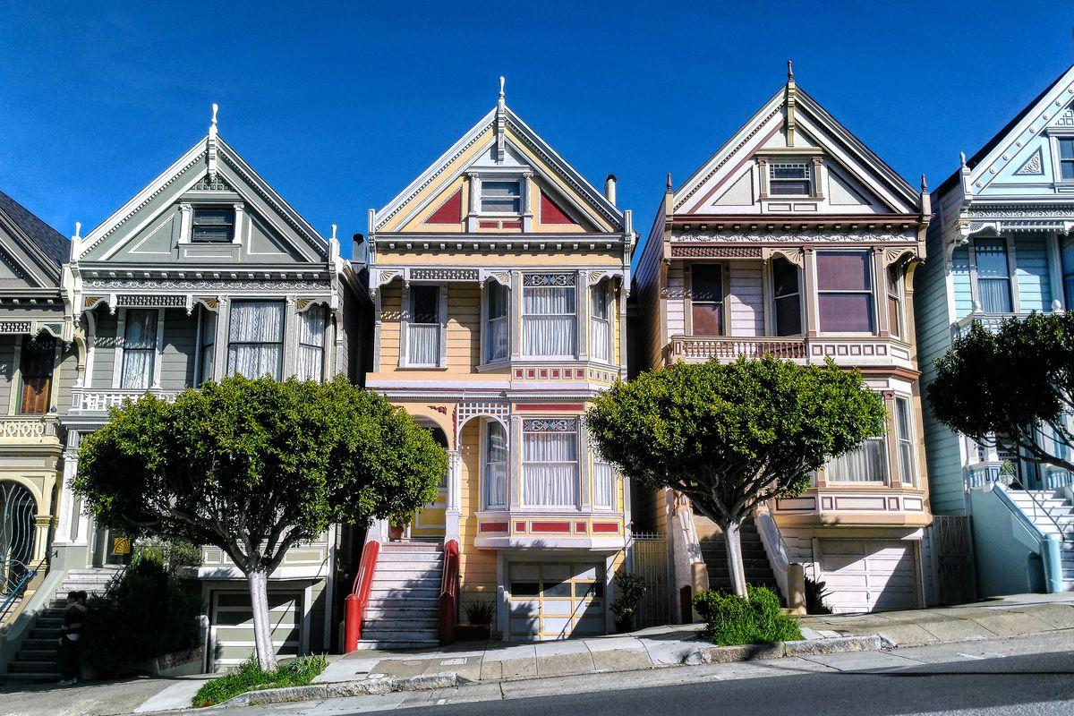 Three row houses sit on a San Francisco street.