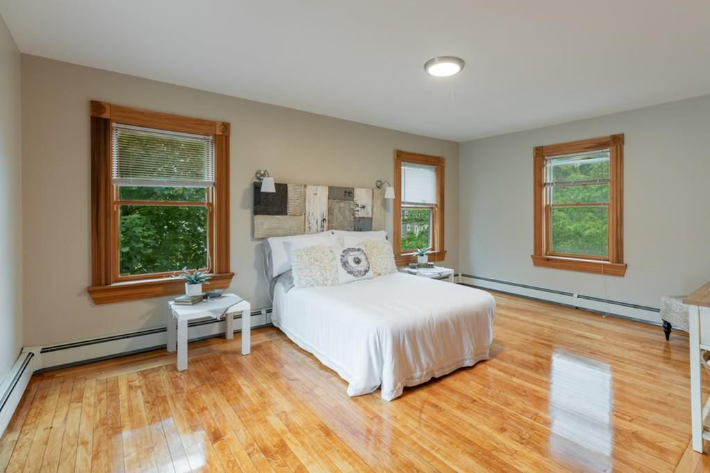 A spacious bedroom with a bed and windows.