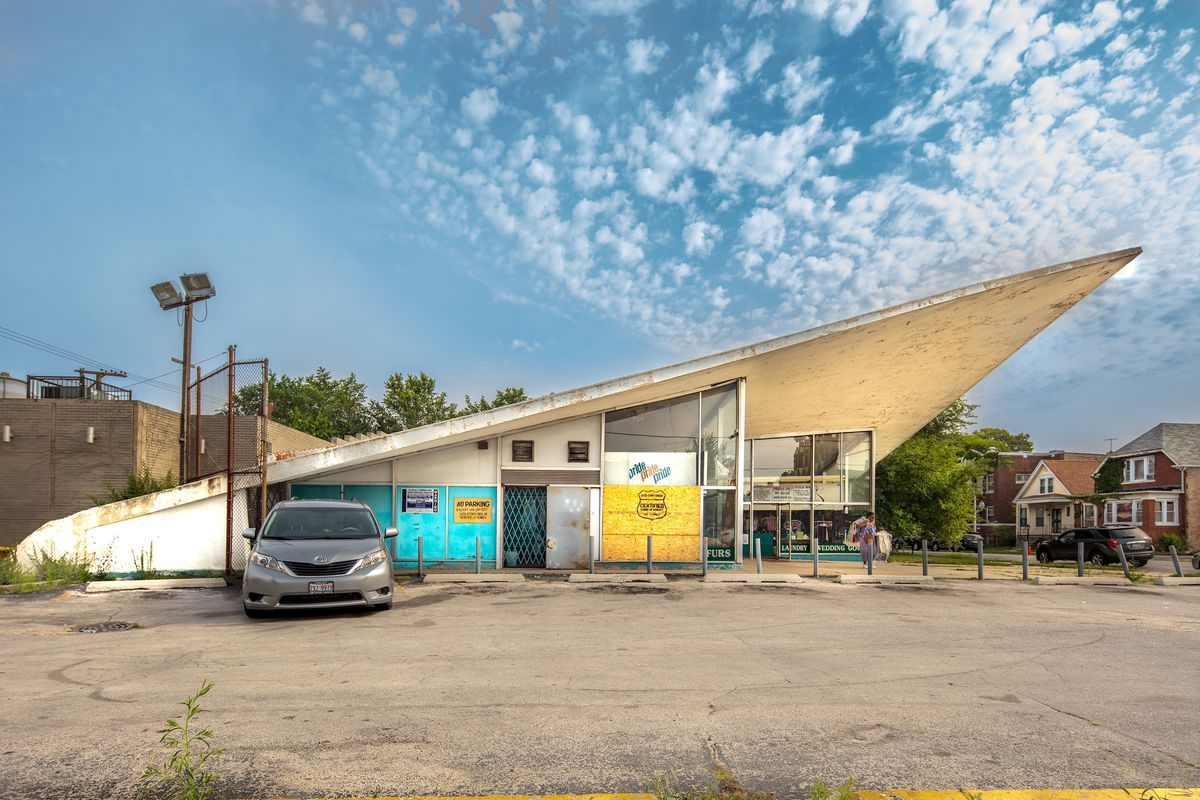 A striking triangle-shaped building with a single sloping roof, storefront windows, and a parking in front.