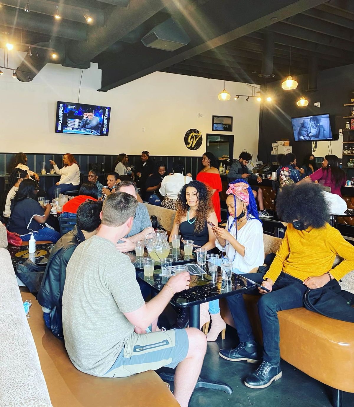 A crowd of people sitting on booths in a bar with drinks on the table and with two televisions on the wall