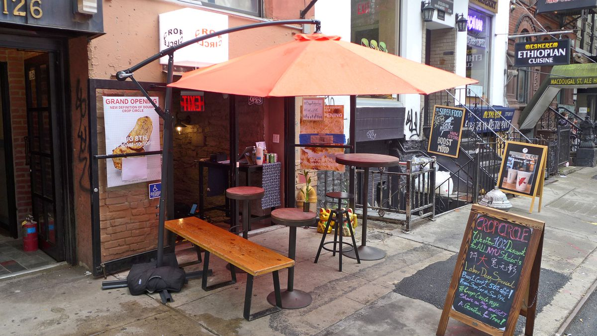 A small doorway with a couple of umbrellaed tables in front.
