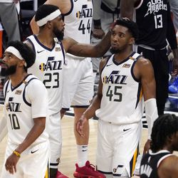Utah Jazz forward Royce O'Neale, center, pats guard Donovan Mitchell, right, on the head as guard Mike Conley walks away in the closing minutes during the second half in Game 6 of a second-round NBA basketball playoff series against the Los Angeles Clippers Friday, June 18, 2021, in Los Angeles.