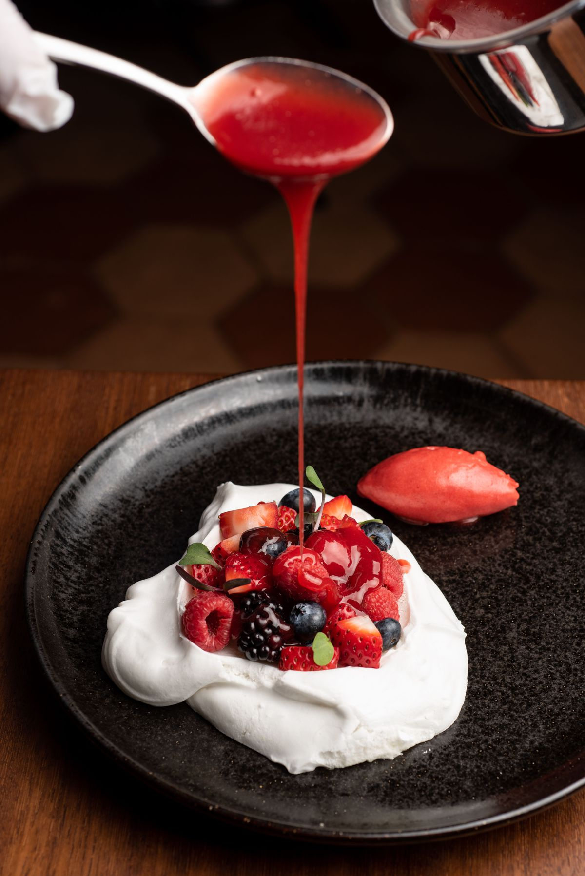 Vegan pavlova with mixed berries and raspberry sorbet on a dark plate.