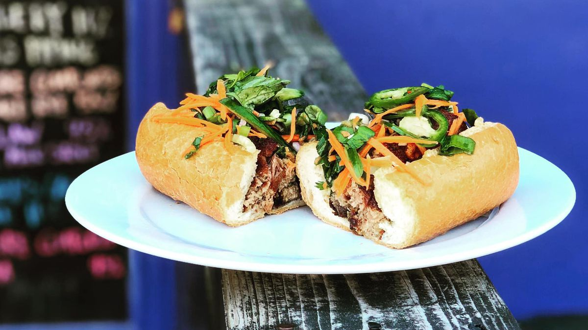 Pork cheek terrine and smoked butt banh mi on a wooden railing topped with sliced carrots and cilantro
