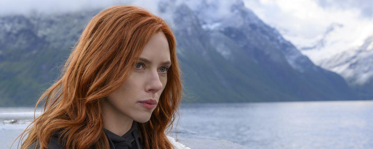 Scarlett Johansson, seen with long red hair standing on a ferryboat in Black Widow