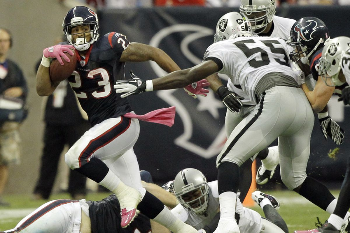 HOUSTON - OCTOBER 09:  Running back Arian Foster #23 of the Houston Texans breaks a tackle by linebacker Rolando McClain #55 of the Oakland Raiders at Reliant Stadium on October 9, 2011 in Houston, Texas.  (Photo by Bob Levey/Getty Images)