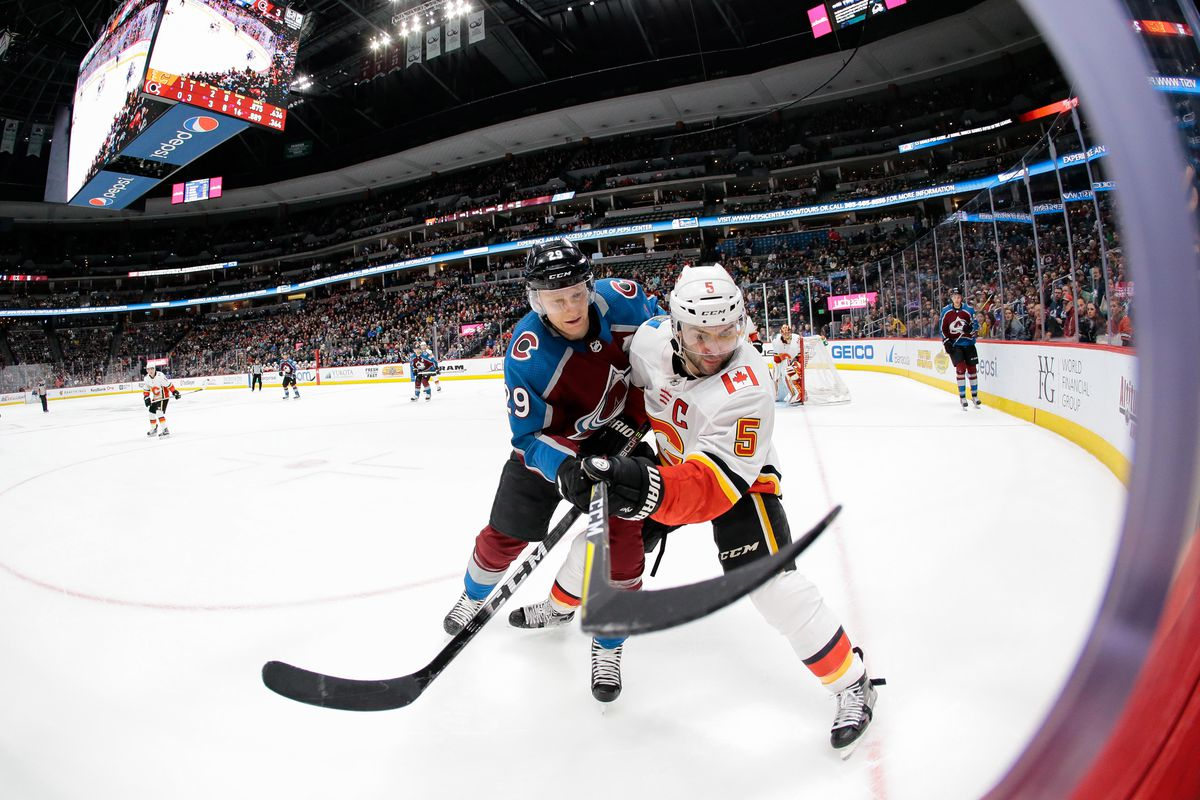 Feb 28, 2018; Denver, CO, USA; Colorado Avalanche center Nathan MacKinnon (29) and Calgary Flames defenseman Mark Giordano (5) battle for the puck in the second period at the Pepsi Center. Mandatory Credit: Isaiah J. Downing
