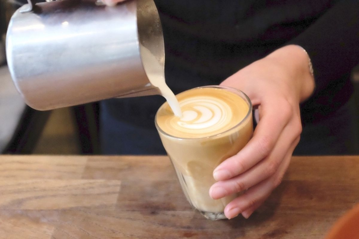 A latte being poured at speciality coffee shop Alchemy Cafe in London